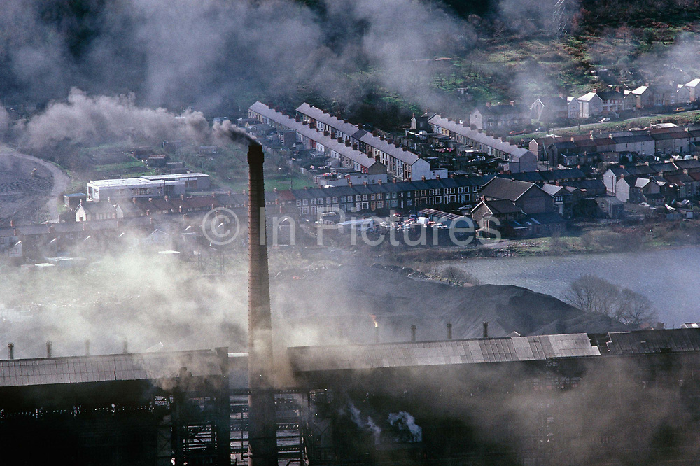 Looking down into a steep-sided valley, Distant streets and working-class terraced homes are beyond smoking chimneys from a Furnacite coking plant at Abercwmboi. Once known as the worst polluter in Britain it was owned by the National Coal Board (NCB) and sold to the Welsh Development Asoociation (WDA) for £1 Pound though arguments are still raging about how to clear it up and cleanup estimates range from £15-£20 million. The pollution had cruel effects on the local population. It made smokeless coal and locals joked that the plant took the smoke out and dumped it on the Cynon Valley but there was concern about toxic waste dumped in the village after the plant's closure and some suffered birth defects. Ironically, the plant was closed because of environmental considerations.