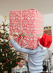 Little boy carrying big cardboard box during Christmas