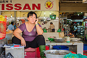 27 MARCH 2012 - HO CHI MINH CITY, VIETNAM:   A fish seller uses her cell phone in Ben Thanh Market, the main market in Ho Chi Minh City, Vietnam. The market has become the main tourist market. Ho Chi Minh City, which used to be known as Saigon, is the largest city in Vietnam and the commercial hub of southern Vietnam.   PHOTO BY JACK KURTZ
