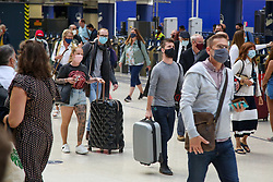 © Licensed to London News Pictures. 08/07/2021. London, UK. Members of the public wearing face coverings with suitcases in Waterloo Station. Transport Secretary, Grant Shapps said to the MPs, that fully vaccinated adults and all children will no longer have to quarantine on their return from amber list countries from 19 July 2021.  Photo credit: Dinendra Haria/LNP
