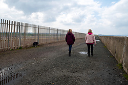 "Cockenzie, East Lothian, UK. 14 April, 2018. Dog walkers at site of the former Cockenzie power station in East Lothian, Scotland. A row has begun over concerns about the Scottish government's decision to ""call in"" a planning application by Red Rock Power to build a renewable energy sub-station on the site. Red Rock Power, part of China's largest state-owned investment fund, the State Development and Investment Corporation (SDIC), wants the the sub-station to allow it  to feed power from the Inch Cape offshore wind farm, near Angus, into the national grid."