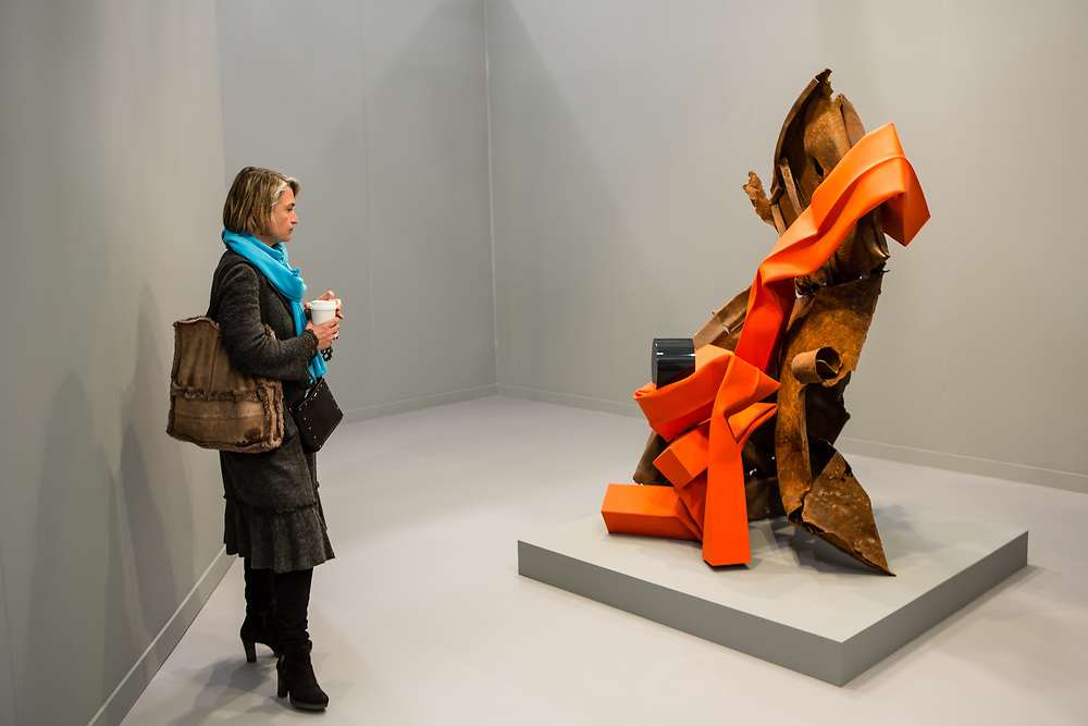 "New York, NY - 5 May 2017. The opening day of the Frieze Art Fair, showcasing modern and contemporary art presented by galleries from around the world, on Randall's Island in New York City. A woman regards Carol Bove's sculpture ""Prélude à l'apres-midi d'une faune."" 2017, in the David Zwirner gallery."