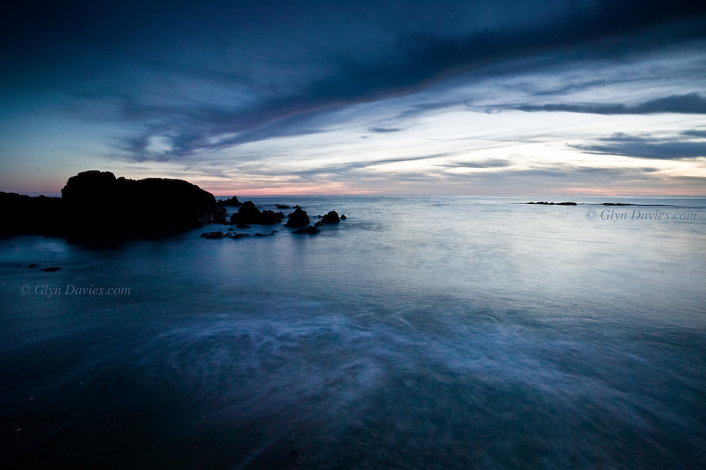 Gentle waves at sunset at the rocky headland between Porth Tyn Tywyn and Broad Beach, Rhosneigr, West Anglesey.