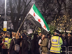 December 13, 2016 - London, London, United Kingdom - Image ¬©Licensed to i-Images Picture Agency. 13/12/2016. London, United Kingdom. Aleppo is Dying Protest. ..A woman holds up a Syrian flag as over 1000 protesters gathered outside the Syrian Embassy in London...As well as voicing their anger at the current dire situation for civilians in the war torn city of Aleppo and speaking out against Bashar al-Assad's regime, Muslim prayers were held at the ''emergency demo.'' ..Picture by Pete Maclaine / i-Images (Credit Image: © Pete Maclaine/i-Images via ZUMA Wire)