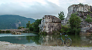 A lone rusty old bicycle stands on the edge of a lake surrounded by mountains and cliffs in Tri Ton, An Giang Province, Vietnam, Southeast Asia