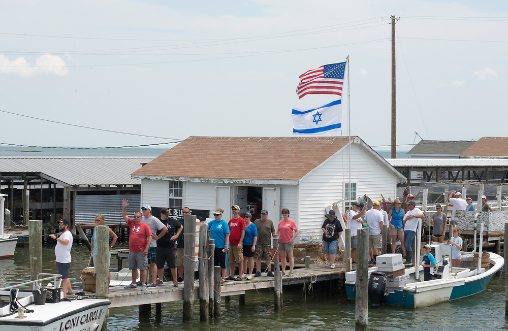 "August 4, 2017 - Tangier Island, VA -  Visitors on the ""waterman's tour""  visit the crab shanty of Tangier Island Mayor James ""Ooker"" Eskridge's crab shack. Set on pilings hundreds of yards from shore, the little shacks, where watermen monitor crabs as they shed their hard shells to become soft-shells, are like Tangier itself: islands apart. Perched 12 miles from the Eastern Shore of Virginia, Tangier (about three miles long and 1 1/2 miles wide) is accessible only by boat or by plane; most visitors take the ferry. Boats outnumber cars, and almost everyone makes a living from the water.Photo by Susana Raab/Institute"