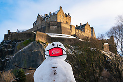 Edinburgh, Scotland, UK. 29 December 2020. A snowman wearing a facemask has been built in Princes Street gardens below Edinburgh Castle following overnight snow in the city. Iain Masterton/Alamy Live News