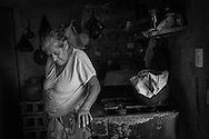 """Elena Giron, 72, in her home in Meanguera,  in the Morazán department of El Salvador, lives alone after many years with her family. """"I used to have a house full of grand children, now they are grown and live somewhere else.  It's very quiet here now"""". (photo by Dana Rene)"""