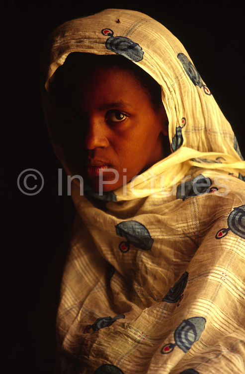 A sad woman in a house in Chinguetti, Mauritania.<br /> Chinguetti, once one of Islam's holiest cities (today it is regarded as the seventh holiest city) it has been dated at a around seven hundred, (700) years old and is famed for it's Koranic libraries and distinctive mosque.