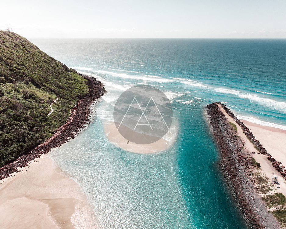Aerial view of Tallebudgera Creek with people standing on a sandbank surrounded by turqoise water and the ocean, Gold Coast, Australia