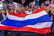 24 JANUARY 2014 - BANGKOK, THAILAND: Thai anti-government protestors wave a Thai flag and cheer for Suthep Thaugsuban when he walked on stage at the Shutdown Bangkok Pathum Wan stage. Shutdown Bangkok has been going for 12 days with no resolution in sight. Suthep, the leader of the anti-government protests and the People's Democratic Reform Committee (PDRC), the umbrella organization of the protests,  is still demanding the caretaker government of Prime Minister Yingluck Shinawatra resign, the PM says she won't resign and intends to go ahead with the election.    PHOTO BY JACK KURTZ