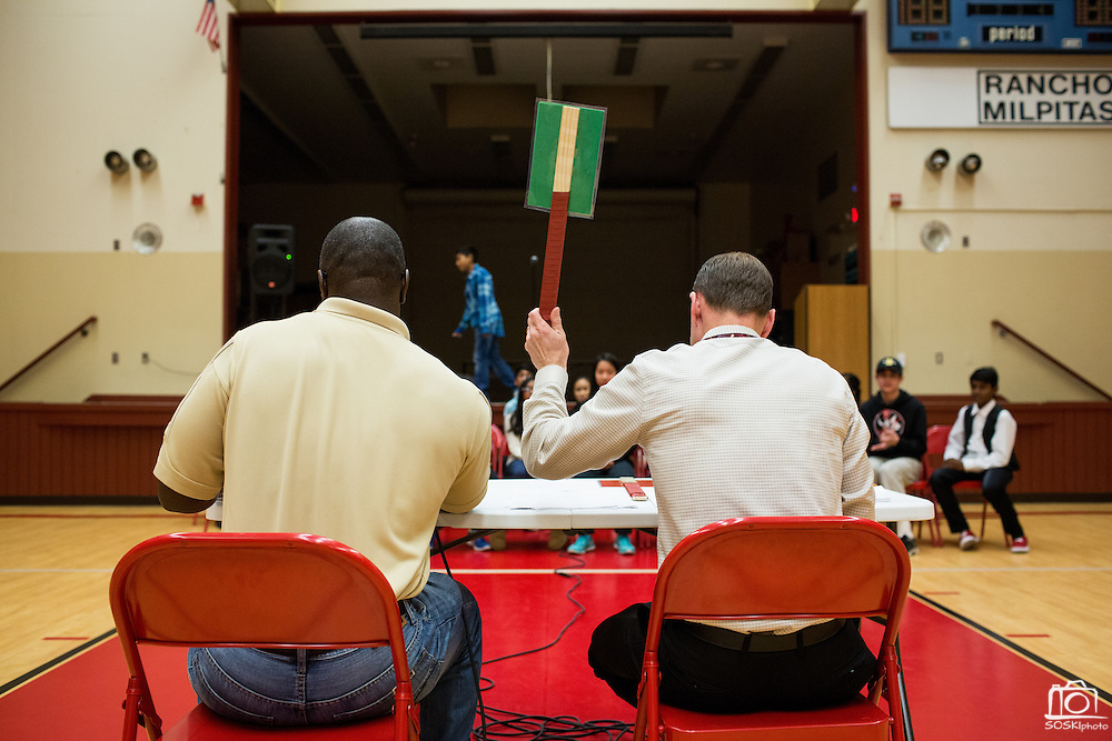 Casey McMurray, right, holds up a green paddle after Jaz Reyes spells a word correctly in an early round of the 1st Annual Spelling Bee at Rancho Middle School in Milpitas, California, on December 9, 2015. (Stan Olszewski/SOSKIphoto)