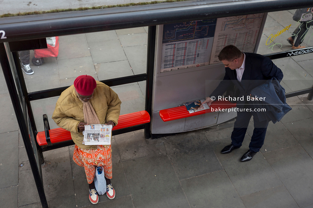 Aerial view of passengers with reading material at a bus stop, on 17th April 2018, in the City of London, England.
