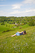 Woman lying on chalk grassland looking into deep green valley containing Rainscombe House, Oare Hill, Wiltshire, England, UK