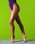 Woman in purple leotard stretching legs. Cropped at abdomen to oiled and tan legs with bright green background