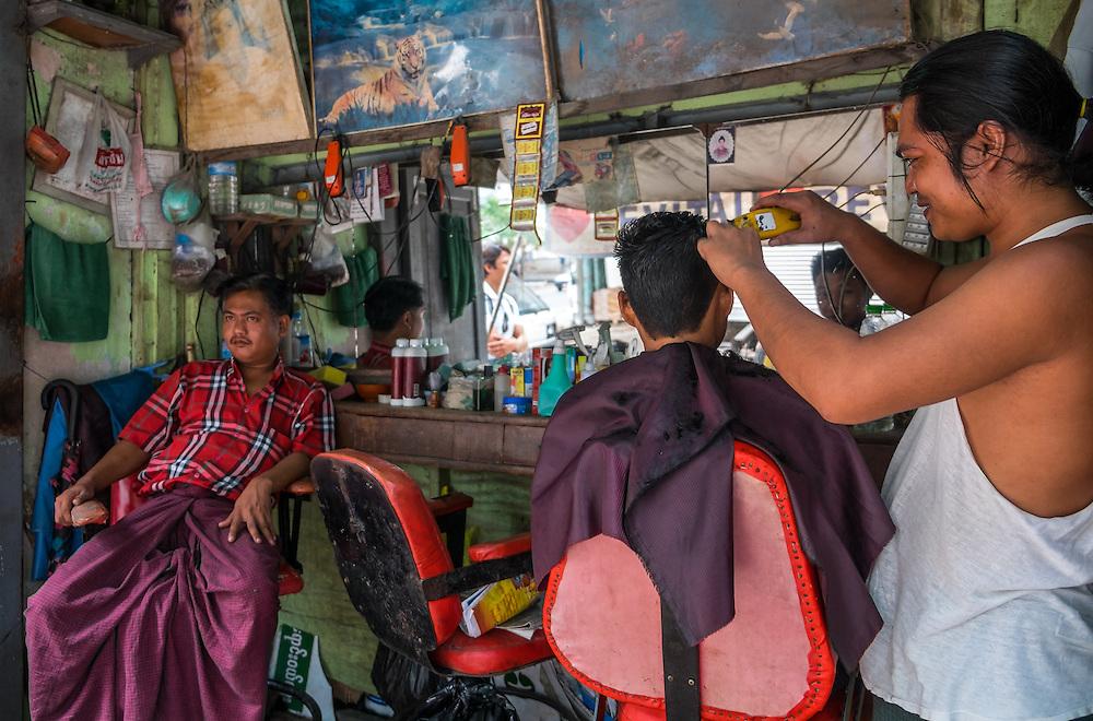 YANGON, MYANMAR - CIRCA DECEMBER 2013: Barbershop in the streets of Yangon.