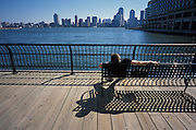 Person relaxing on a bench by the river