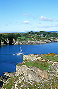 Yacht in channel view to Sherkin Island cliffs from Baltimore, County Cork, Ireland
