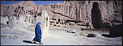 A burqa-clad woman walks past the blown-up Buddha statues in Bamiyan. The two Buddha statues were blown up and destroyed in March 2001 by the Taliban, on orders from leader Mullah Mohammed Omar, after the Taliban government declared that they were idols.