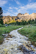 A stream flows from le Coronelle in the Rosengarten/Catinaccio group at sunrise in the Dolomites, Italy, Europe. From Pera di Fassa village (in Pozza di Fassa comune in Val di Fassa), in Trentino-Alto Adige/Südtirol region, Italy, take a bus or lift to visit Rifugio Gardeccia Hutte and hike in the Rosengarten mountain massif (Catinaccio Group) of the Dolomites. 200 million years ago, Triassic coral reefs fossilized into Dolomite. Collision of tectonic plates lifted the Dolomites within the Southern Limestone Alps. UNESCO honored the Dolomites as a natural World Heritage Site in 2009. This panorama was stitched from 6 overlapping photos.