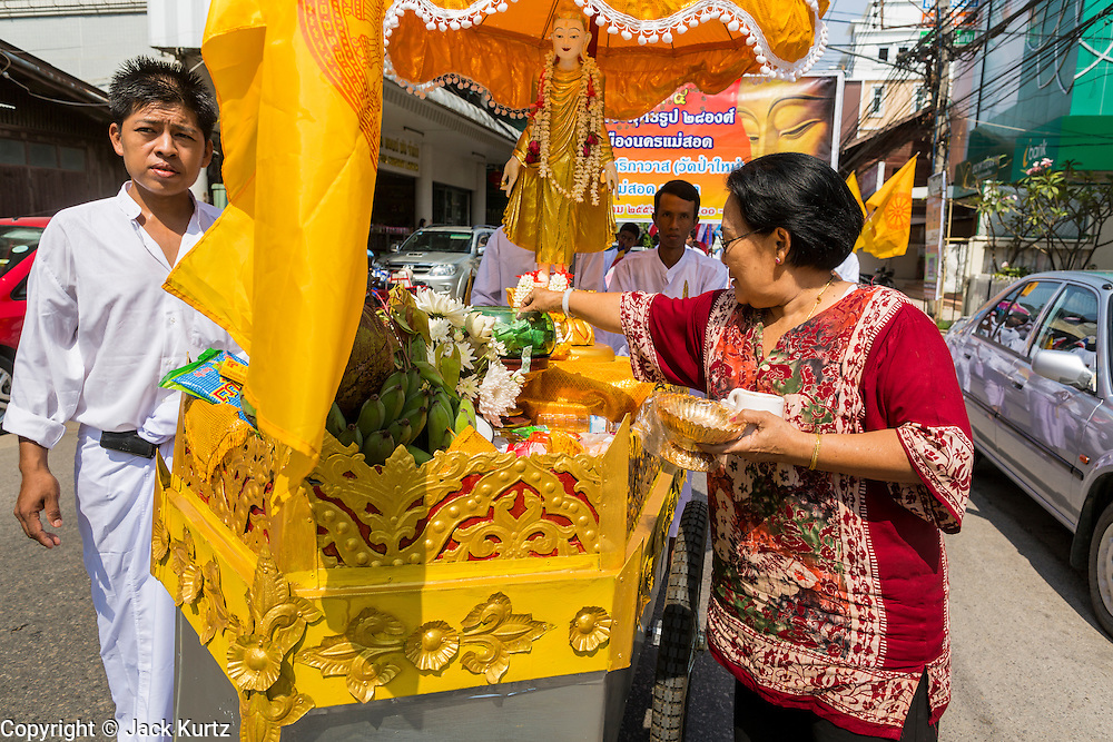24 MAY 2013 - MAE SOT, THAILAND:  A Thai woman donates money to the local Burmese Buddhist temple in Mae Sot, Thailand, during a procession for Visakha Puja Day. Visakha Puja (Vesak) marks three important events in the Buddha's life: his birth, his attainment of enlightenment and his death. It is celebrated on the full moon of the sixth lunar month, usually in May on the Gregorian calendar. This year it is on May 24 in Thailand and Myanmar. It is celebrated throughout the Buddhist world and is considered one of the holiest Buddhist holidays. Burmese Buddhist in Mae Sot celebrated with a procession through Mae Sot that ended with a service followed by a communal meal at Wat Pha Mai, the most important Burmese Buddhist temple in Mae Sot.   PHOTO BY JACK KURTZ