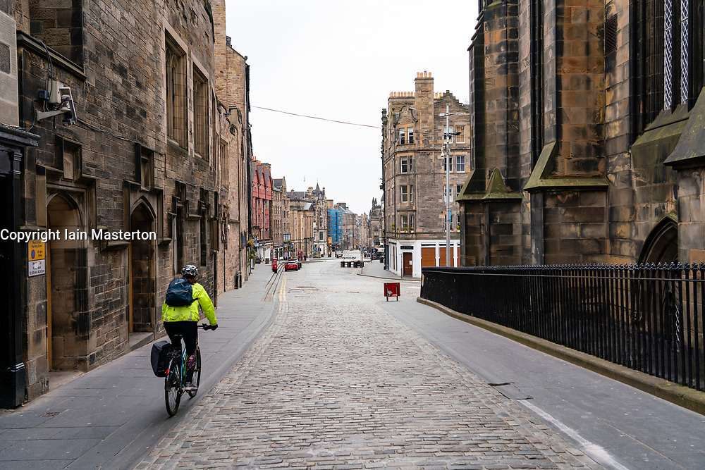 Edinburgh, Scotland, UK. 24 March, 2020.  Deserted streets in the heart of the Old Town tourist district in Edinburgh. All shops and restaurants are closed with very few people venturing outside following the Government imposed lockdown today. Pictured; Lone cyclist on empty streets at Lawnmarket on the Royal Mile. Iain Masterton/Alamy Live News