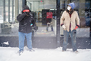 29 DECEMBER 2020 - DES MOINES, IOWA: Homeless men in downtown Des Moines wait for a bus to take them to a shelter during the heaviest snowfall so far of the 2020-21 winter. Des Moines was expected to get about 8 inches of snow before Wednesday morning. Statewide, across Iowa, more than 900 snowplows have been called out to clear the roads.       PHOTO BY JACK KURTZ