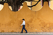 A Mexican cowboy walks past a colorful wall through the streets of San Miguel de Allende, Mexico.