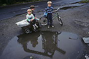Children play near a puddle in the town of Nova Huta. In filthy industrial streets, the kids look undernourished in this scene of impoverished, Communist dereliction. It is horribly depressing and unhealthy place to grow up and these children are pale and yet seem happy, with smiles on their faces. The famous steel works can be seen reflected in the puddle before them. After the war, Stalin decided to build an industrial Communist fantasy just outside Krakow: a model town and immense steelworks of the future. The steelworks was named after Lenin and the town would be called Nowa Huta  - or, the new steel mill. At its peak, 27,000 people worked at the Lenin Steelworks. But Solidarity grew strong forcing strikes over pay and recognition over their union. Today, it is an economic and ecological disaster area..