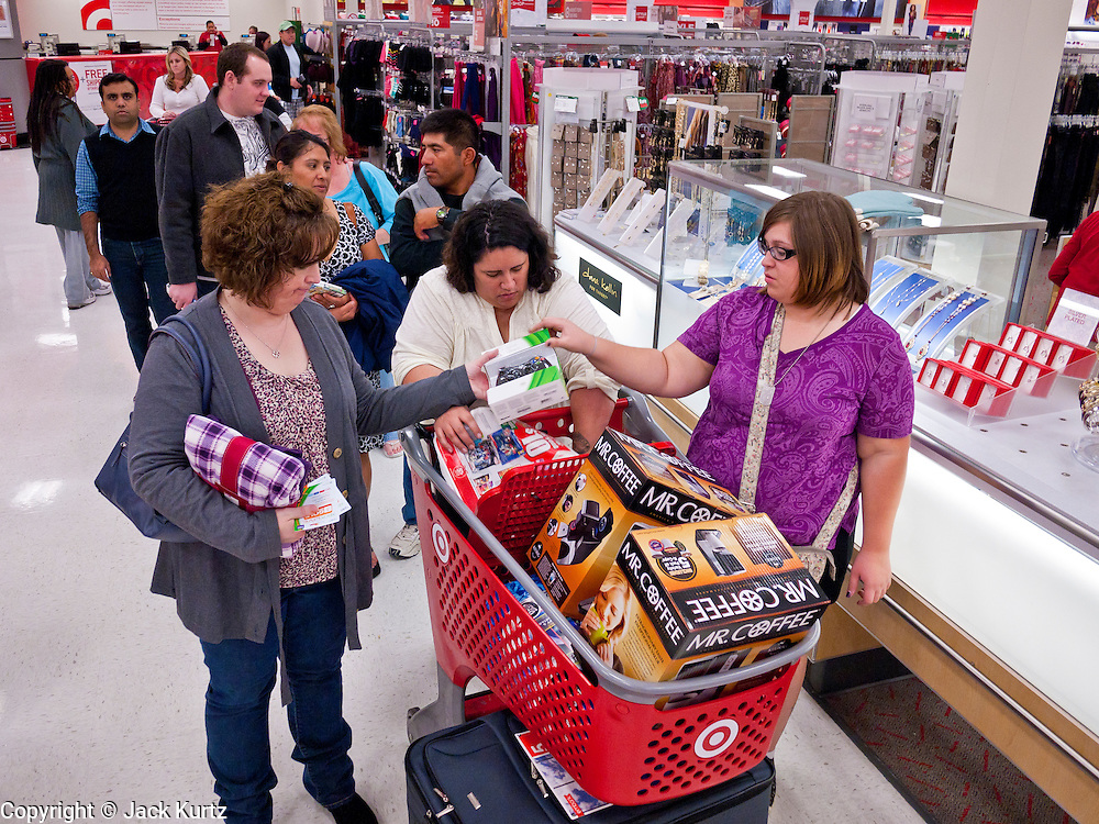 """25 NOVEMBER 2011 - PHOENIX, AZ:  L to R: Kelly Lloyd (CQ), from Phoenix, Oat Craig (CQ) from Maricopa and her daughter Samanth Craig (CQ) also from Maricopa, wait in line to check out in the Target Store across the street from Paradise Valley Mall Friday morning. """"Black Friday,"""" the unofficial start of the holiday shopping season started even earlier than normal. Many stores, including Target and Best Buy, opened at midnight.    Photo by Jack Kurtz"""
