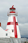 The red and white paint of the East Quoddy Lighthouse gleams in a ray of sun against a stormy gray sky.