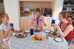 Siblings with carer eating a meal.