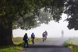 Licensed to London News Pictures. 06/09/2021. London, UK. Cyclist enjoy a warm misty start to the day in Richmond Park, south-west London as weather forecaster predict a mini-heatwave for September this week with temperatures hitting over 29c tomorrow. Photo credit: Alex Lentati/LNP
