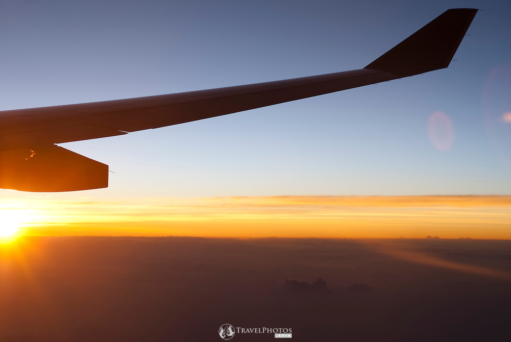The wingtip of a Singapore Airlines Airbus A330-300 at dawn over an overcast sky over the Pacific Ocean