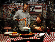 """Aziz Ansari and Jesse Eisenberg serve up pizza at Gino's East in Chicago while promoting their new movie """"30 Minutes or Less"""" on Thursday, July 7, 2011."""