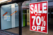 Shop window of an empty retail unit in Middlesborough town centre, North Yorkshire, United Kingdom.  The windows still have the sale signs on display with all prices reduced and up to 70% off. It was forced to close down due to the economic down-turn.