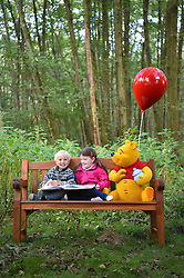 EDITORIAL USE ONLY<br /> Four year old Jacob O'Dell (left) and Hetti Arnett sit on a bench, known as a 'Thotful Spot', that talks to you when you sit on it, at '100 Acre Woods' in Ashdown Forest, to celebrate the 90th anniversary of the publication of AA Milne's first collection of stories about Winnie-the-Pooh this Friday.