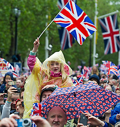 © London News Pictures. 05/06/2012. London, UK.  A girl in a poncho in the rain waving a union flag as the red arrows perform a flypast over Buckingham Palace on June 5, 2012 as part of the Diamond Jubilee celebrations.  Photo credit: Ben Cawthra/LNP