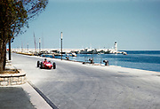 Formula One motor racing Monaco Grand Prix race 1961, Richie Ginther in Ferrari 156 F1 sharknose car approaching tobacconist kiosk