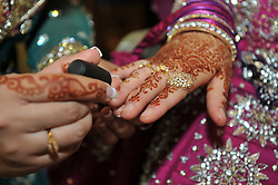 Close up of Pakistani bride preparing for her wedding day, with henna, jewellery and nail polish.