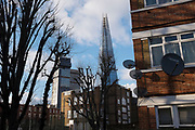 The Shard towering over a council housing estate covered in satellite dishes in Southwark, London, UK. The Shard, also referred to as the Shard of Glass, Shard London Bridge and formerly London Bridge Tower, is an 87-storey skyscraper in London that forms part of the London Bridge Quarter development.