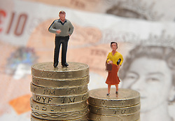 File photo dated 27/01/15 of plastic models of a man and woman standing on a pile of coins and bank notes, as it has been warned that the gender pay gap will remain for a lifetime unless the Government and employers do more to tackle the difference between the wages of men and women.