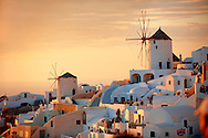 Oia ( Ia ) Santorini - Windmills and town at sunset, Greek Cyclades islands - Photos, pictures and images .<br /> <br /> If you prefer to buy from our ALAMY PHOTO LIBRARY  Collection visit : https://www.alamy.com/portfolio/paul-williams-funkystock/santorini-greece.html<br /> <br /> Visit our PHOTO COLLECTIONS OF GREECE for more photos to download or buy as wall art prints https://funkystock.photoshelter.com/gallery-collection/Pictures-Images-of-Greece-Photos-of-Greek-Historic-Landmark-Sites/C0000w6e8OkknEb8