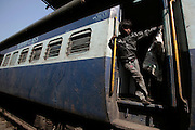 Badal rides the train as it slows to a stop at the Jaipur train station before raiding it for plastic bottles.  Children, some who have run away from their families, find themselves living homeless on the train tracks waititng for the next train to arrive at the train station in Jaipur, India.  Once the train arrives they raid the train looking for plastic bottles that they can then sell.  Most will make about $1.50/day but spend most of it on glue which they are most addicted to.