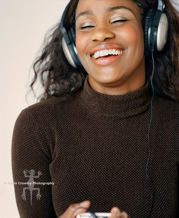 Young African-American woman listening music on a mp3 player (ipod).