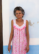 Elderly woman in pink dress smoking cigarette, Remedios, Cuba