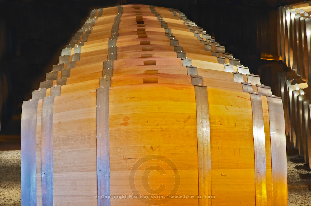 The barrel ageing cellar with rows and stacks of oak barriques against a black background Chateau Thieuley La Sauve Majeure Entre-deux-Mers Bordeaux Gironde Aquitaine France