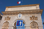The French national flag flies on top of the 17th century Arc de Triomphe, with a traffic sign showing priority for one direction, on 17th June 2016, in Montpellier, France. Looking up at the Romanesque arch, built to honour King Louis XIV where once stood ancient ramparts, is now the entrance to the inner city of this provincial town.
