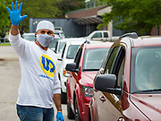 21 MAY 2020 - DES MOINES, IOWA: IZAAH KNOX, the executive director of Urban Dreams, directs traffic and signals the number of meals people want at a drive through emergency food distribution in Evelyn K. Davis Park in central Des Moines. All of the 485 meals were distributed in about an hour. The economic fallout of the pandemic is being felt throughout Iowa. On May 21, 2020, Iowa reported that 187,375 people had filed for unemployment since the beginning of the COVID-19 pandemic and resulting economic shutdown. Emergency food pantry has also increased in that time, as many Iowans in low wage jobs used emergency food banks and pantries for the first time. The Food Bank of Iowa said Thursday that demand in April 2020 was 31% higher than demand in April 2019, mostly because of unemployment caused by the Coronavirus (SARS-CoV-2) pandemic. The emergency food distribution Thursday was organized by the city of Des Moines, Food Bank of Iowa, Central Iowa Shelter and Services, Urban Dreams and Orchestrate Hospitality.     PHOTO BY JACK KURTZ