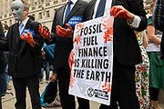 A group of Extinction Rebellion protestors dressed in suits as faceless financiers with fake blood on their hands, and one of them holding a placard about fossil fuels on 27th August, 2021 in London, United Kingdom. The activist group Extinction Rebellion XR are planning actions of disruption for two weeks straight beginning on August 23rd, 2021 in an effort to bring awareness and priority to the global climate emergency in advance of the COP 26 Summit which will be held in Glasgow later this year.